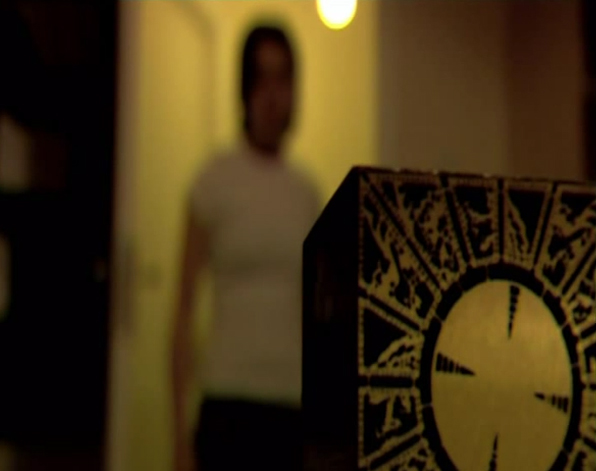 A still from The Hellraiser Chronicles: Lifebringer. A blurred figure enters a room, the strange device rests on the table inside.